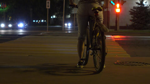 Female biker standing at red light on crosswalk. Traffic light. 4K shot Footage