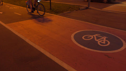 Two bicycles passing by on urban bike path at night. 4K shot Footage