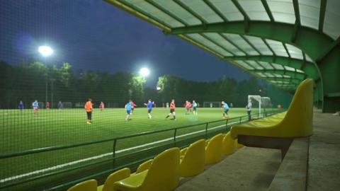 Amateur football game slow motion bokeh video. Empty tribune wide view Footage