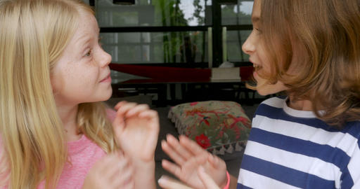 Two young happy smiling girls whispering and telling secrets to each other Footage