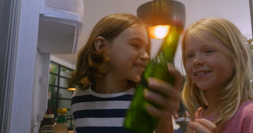 Two young girls open a refrigerator door and take a green bottle out pov from Footage