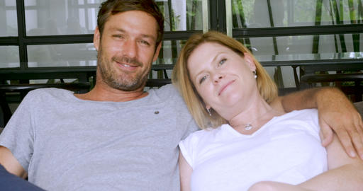 Loving happy attractive couple in their 40s smiling and sitting on a sofa Footage