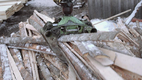 Truck loader crane claw picks up sawmill wooden waste Live Action
