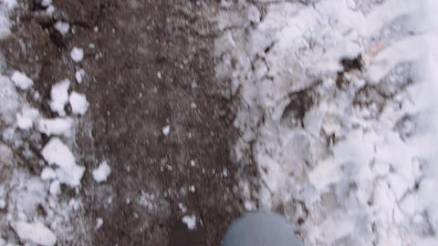 POV man in dark boots walking on dirty road at winter Footage