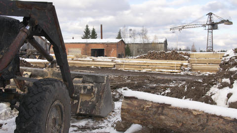 Excavator at woodwork yard stored piles of lumber materials covered in snow Footage