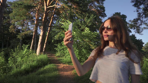 Young long hair brunette girl in sunglasses making selfie with her phone in Footage
