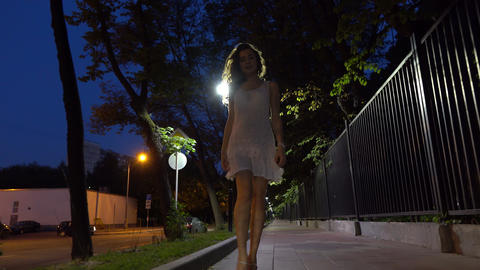 Beautiful brunette girl walking at camera on night street steadicam 4K shot Footage