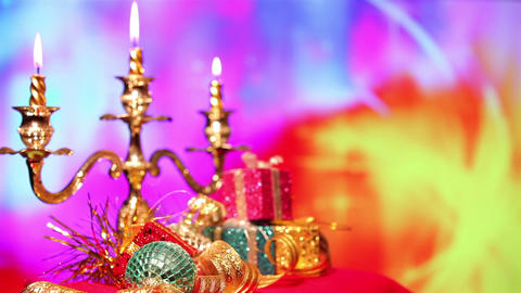 Christmas gift and candle on defocused lights background Stock Video Footage