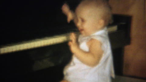 1963: Cute blonde baby learning piano plays keys smiles laughs Footage