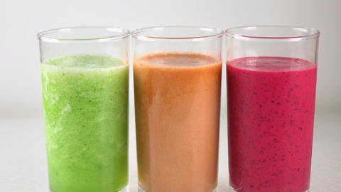 Three glasses of multicolored vegetable smoothies. 4K dolly video Footage