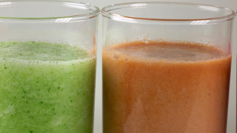 Three glasses of multicolored vegetable smoothies. 4K dolly macro video Footage
