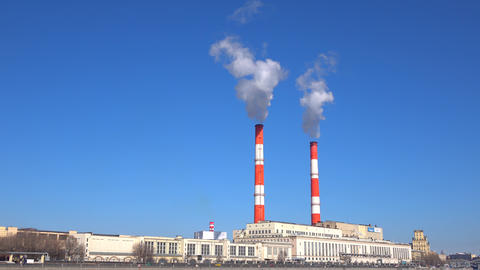 Old heat electric plant and smoke from stacks against blue sky. 4K video Footage