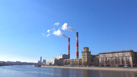 Heat electric plant and smoke from smoke stacks against blue sunny sky. 4K shot Footage