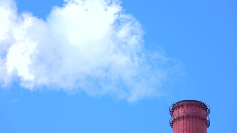 Smoking red smoke stack top against sunny blue sky. 4K telephoto lens shot Footage