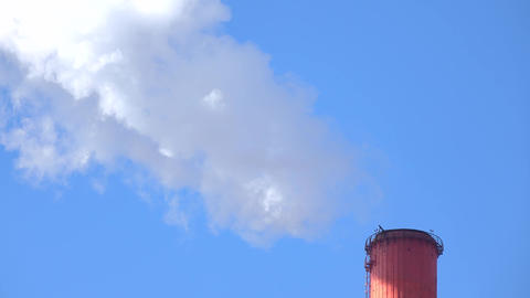 Smoking red smoke stack against sunny blue sky. 4K telephoto lens video Footage