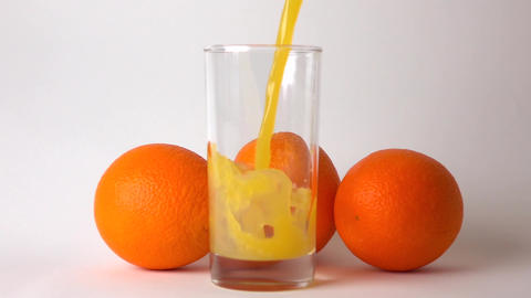 Three whole oranges and orange juice being poured into glass. Super slow motion Live Action