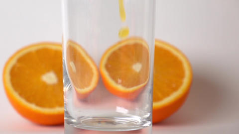 Two orange halves and orange juice being poured into glass. Super slow motion Footage