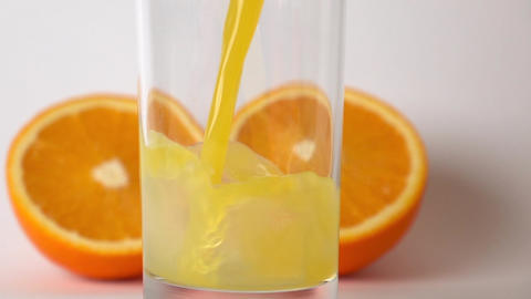 Two orange halves and orange juice being poured into... Stock Video Footage