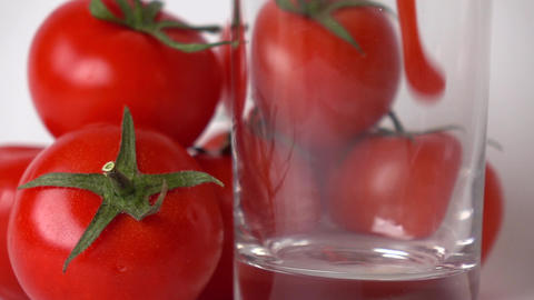 Some red tomatoes and tomato juice being poured into glass. Super slow motion Footage