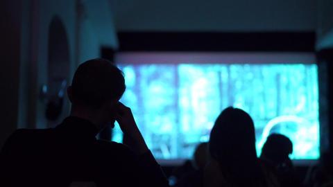 Silhouettes of people watching movie in dark cinema hall Footage