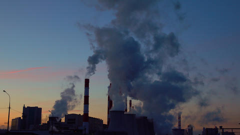 Steaming and smoking factory stacks against late sunset sky. 4K shot Footage