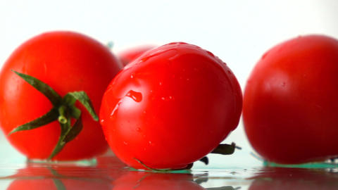 Red ripe tomatoes hit wet glass surface with splashes and rebound. Slow motion Footage