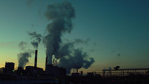 Silhouette of polluting obsolete plant against late sunset sky. 4K video Footage