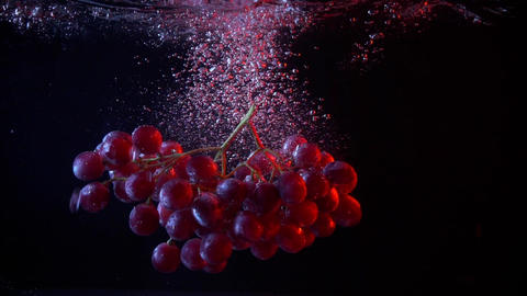 Red grapes fall into water with splashes super slow motion shot Footage