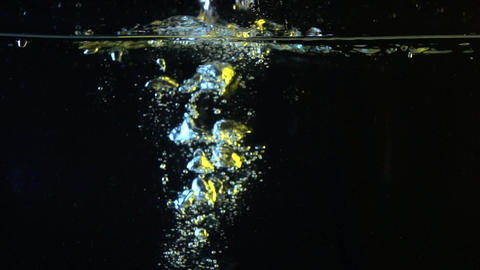 Lemon falling into water super slow motion shot against black background Footage