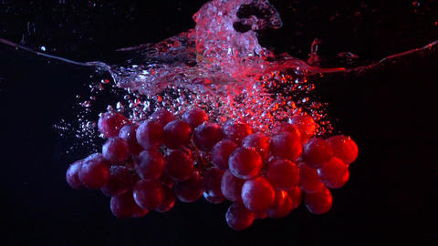 Bunch of red grapes falling into water with splashes super slow motion shot Footage
