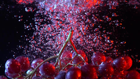 Bunch of red grapes falling into water close up super slow motion shot Footage