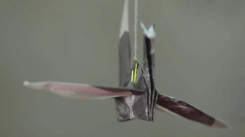 Paper origami crane rotating on thread against gray background Live Action