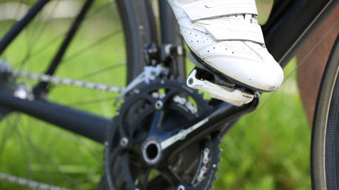 Sportsman puts his foot on the pedal of his of black road bicycle. Close up shot Live Action