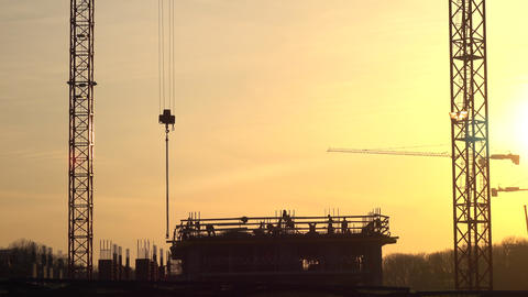 Silhouettes of cranes and construction site workers against orange sunset. 4K Footage