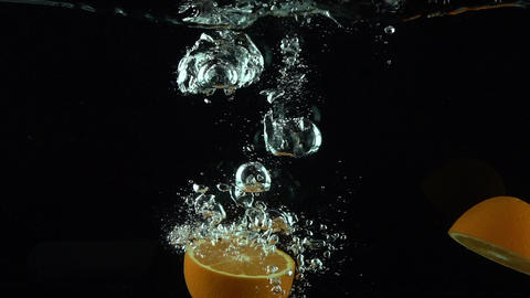 Orange splits into halves and sinks in water super slow motion video Footage