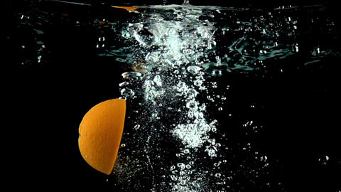 Close up super slow motion video of orange splits into halves and sinks in water Footage