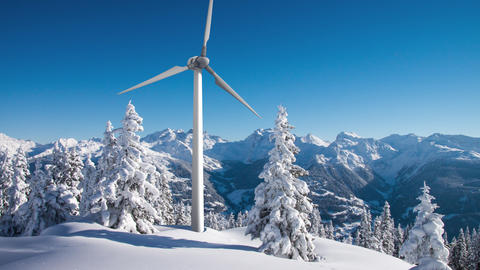 Rotating wind turbine above sunny snowy forest in the mountains 4K footage Footage