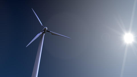 Single rotating wind turbine against blue sky and blazing sun 4K dolly shot Footage