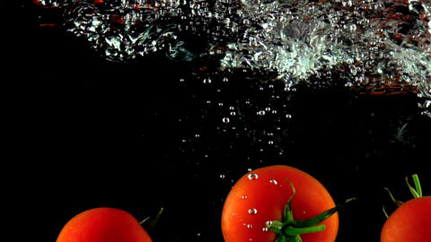 Super slow motion close up shot of hand reaching and grabbing tomato under water Live Action