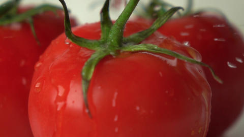 Multiple water drops hit red ripe tomato with green leaves super slow motion Footage