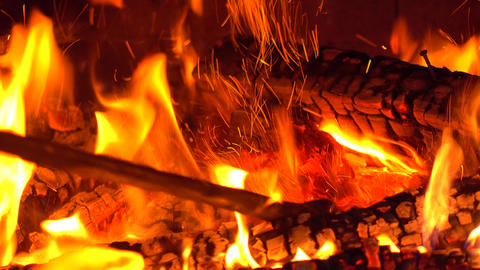Stirring burning firewood at brick fireplace with a poker 4K video Footage