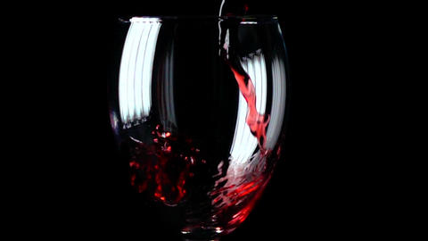 Filling wine glass with red wine super slow motion macro shot, black background Footage