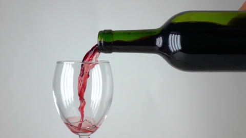 Pouring red wine into a glass, gray background, super slow motion close up shot Footage