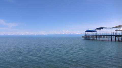 Empty pier, lake and distant snow peaks on the horizon. 4K sunny day pan shot Footage