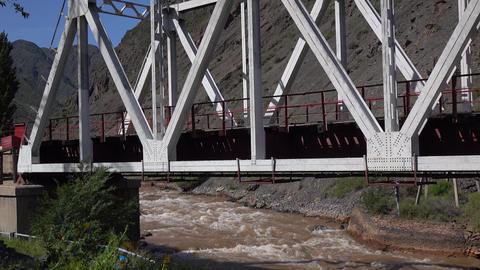 Old steel railroad bridge above fast mountain river rapids. 4K pan shot Footage