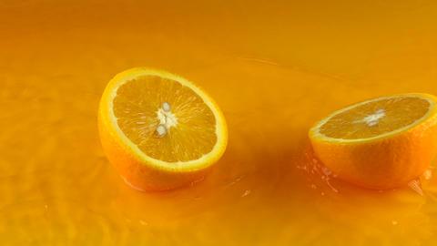 Orange falls on orange juice surface and splits into halves. Slow motion video Footage