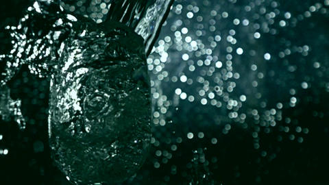 Super slow motion low key shot of water being poured in glass. Bokeh background Footage