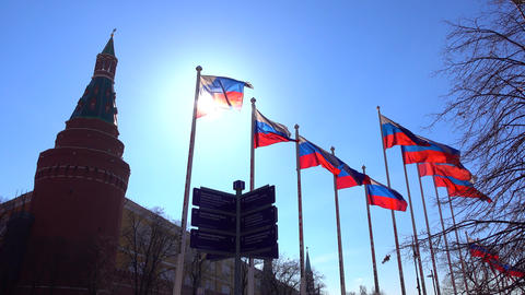 Soaring Russian flags near the Moscow Kremlin against sunny blue sky. 4K video Footage
