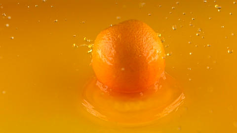 Whole ripe orange hitting orange juice surface and rebouncing. Slow motion shot Footage