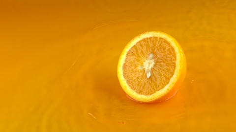 Half of ripe orange hits orange juice surface and rebounces. Slow motion video Live Action